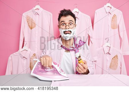 Shocked Caucasian Man Dressed In Formal Clothes Applies Foaming Gel Shaves And Irones Clothes At Sam
