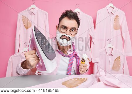 Serious Man Has Attentive Gaze At Camera Shaves While Doing Ironing Dresses For Special Occasion Wea