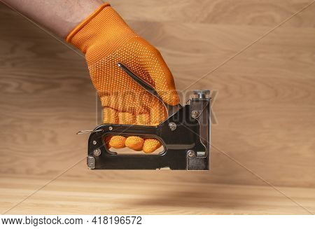 Construction Stapler In Male Hand In Building Orange Glove. Tool For Repair.
