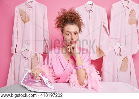 Serious Curly Haired Woman Looks Seriously At Camera Wears Dressing Gown Poses Near Ironing Board Ha