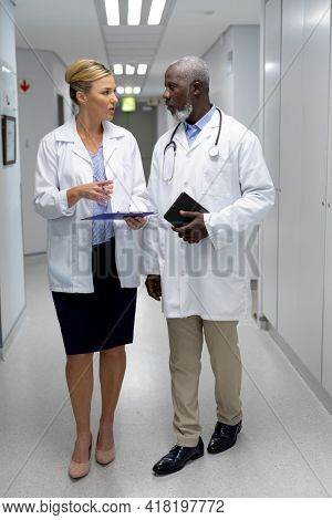 Diverse male and female doctors walking through hospital corridor and talking. medicine, health and healthcare services.