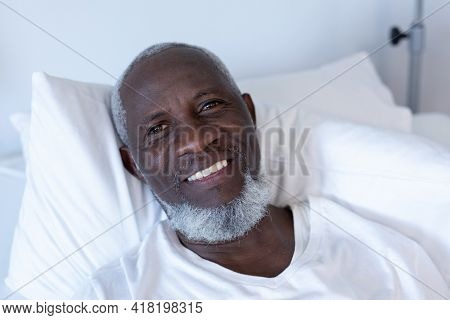 Portrait of african american male patient lying on hospital bed smiling to camera. medicine, health and healthcare services.