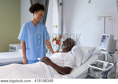 Mixed race female doctor and african american male smiling to each other in hospital patient room. medicine, health and healthcare services.