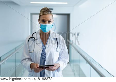 Portrait of caucasian female doctor wearing mask standing in hospital corridor holding tablet. medicine, health and healthcare services during coronavirus covid 19 pandemic.