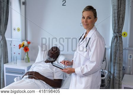Caucasian female doctor standing next to male in patient room holding tablet looking to camera. medicine, health and healthcare services.