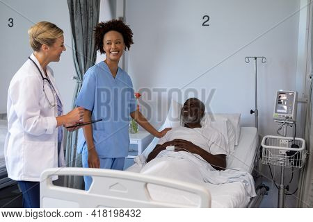 Two diverse female doctors and african american male patient in hospital room smiling to each other. medicine, health and healthcare services.