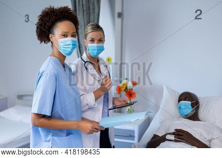 Portrait of two diverse female doctors wearing face masks standing next to male patient. medicine, health and healthcare services during coronavirus covid 19 pandemic.
