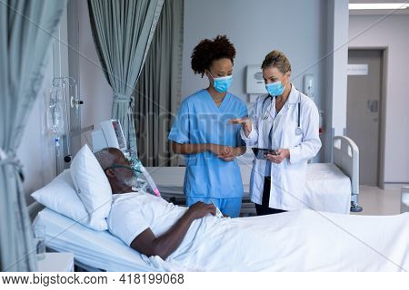 Two diverse female doctors talking to african american male in hospital patient room. medicine, health and healthcare services during coronavirus covid 19 pandemic.