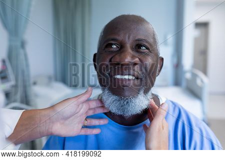 Caucasian female doctor palpating lymph nodes of african american male patient. medicine, health and healthcare services