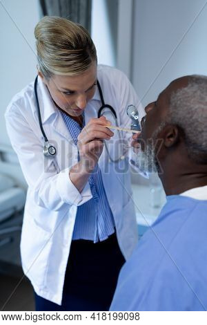 Caucasian female doctor examining throat of african american male patient. medicine, health and healthcare services