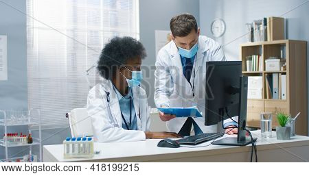 Mixed-race Male And Female Doctors In Medical Masks Speaking Discussing Analysis Results Working In