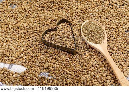 Cannabis Seeds With A Heart. Ground Organic Hemp Seed. Texture. Hemp Seeds Background