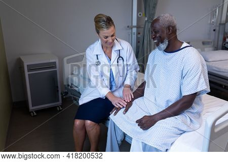 Caucasian female doctor sitting on hospital bed touching hand of african american male and smiling. medicine, health and healthcare services.
