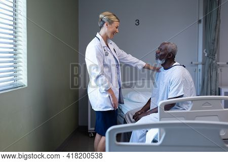 Caucasian female doctor smiling to african american male patient in hospital room. medicine, health and healthcare services.