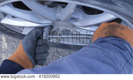 Hands With Gloves Forcefully Unscrew Or Tighten The Bolt In The Structure Of The Car Wheel When Inst