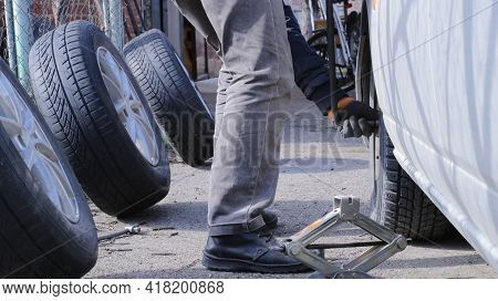 Changing Wheels In The Spring Season In The Conditions Of His Own Garage, A Man Changes Wheels On A