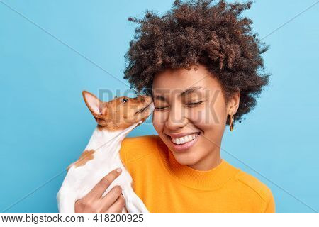 Friend Of Family. Close Up Shot Of Happy Curly Haired Woman Plays With Dog Expresses Positive Emotio