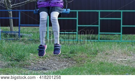 Legs In Striped Tights Of A Girl Sitting On A Swing Over The Green Grass Of A Spring Lawn, A Lonely