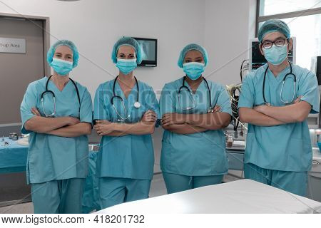 Diverse group of male and female doctors standing in operating theatre wearing face masks. medicine, health and healthcare services during coronavirus covid 19 pandemic.