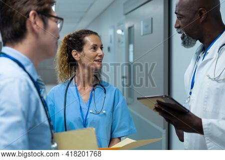 Diverse group of male and female doctors standing discussing on corridor. medicine, health and healthcare services.