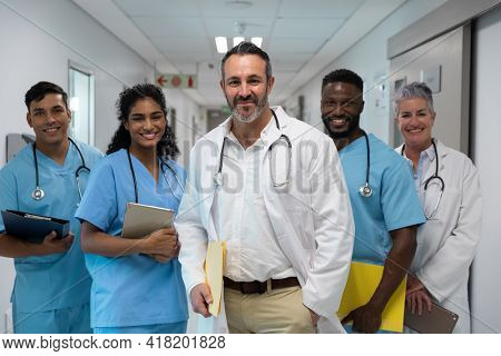 Portrait of diverse group of male and female doctors holding files, smiling in hospital corridor. medicine, health and healthcare services.