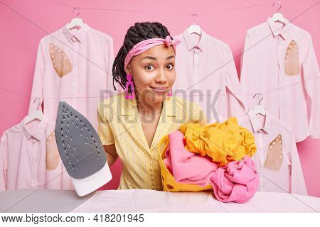 Beautiful Dark Skinned Afro American Woman Wears Headband Carries Basket Full Of Washed Laundry Hold