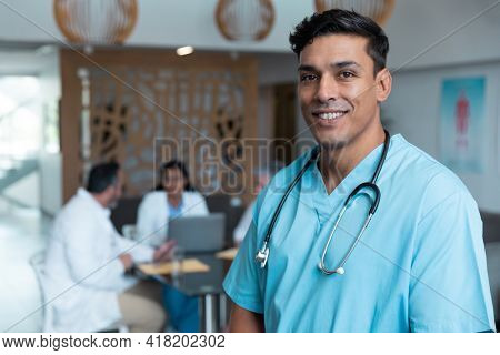 Portrait of smiling mixed race male doctor with colleagues in discussion in the background. medicine, health and healthcare services.