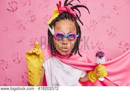 Photo Of Attentive Serious Housewife Wears Goggles Superhero Cape And Rubber Gloves Holds Brush For