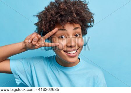 Optimistic Teenage Girl With Curly Bushy Hair Makes Peace Sign Over Face Smiles Happily Enjoys Excel