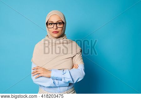 Portrait Of Serious Young Arab Woman Wearing Hijab And Glasses Standing Against Blue Background With