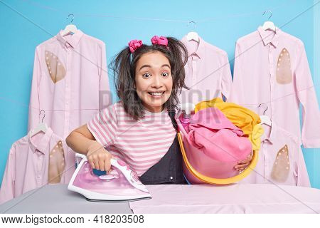 Smiling Glad Brunette Housewife Irons Clothes At Home Uses Electric Steam Iron Dressed In Casual T S