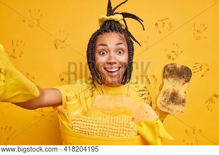 Happy Ethnic Woman Does Housework And Cleaning Makes Selfie Holds Dirty Sponge Wears Rubber Gloves S