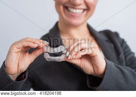 A Woman Is Holding A Transparent Plastic Mouth Guard. Orthodontists Bite Correction Device