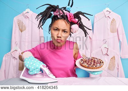 Dissatisfied Afro American Woman Busy Doing Housework Irons Clothes With Electric Iron Holds Plate O