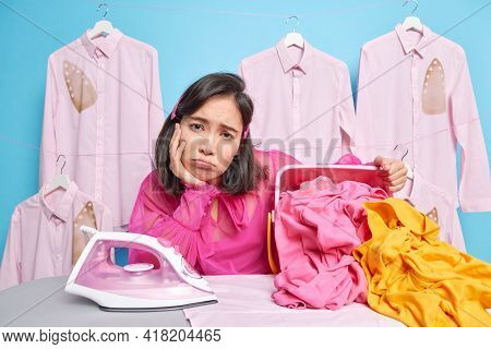 Overworked Asian Woman Looks Sadly At Camera Leans At Ironing Board Irones Clothes Prepares Laundry
