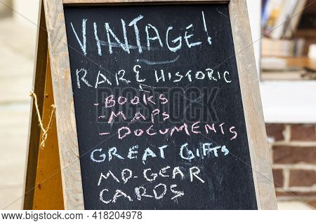 A Small Business Selling Local Items And Gifts As Put Up A Sandwich Board With Select Inventory Cate