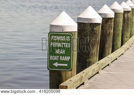 Fishing Is Permitted Near Boat Ramp Sign On Green Metal Plate Attached To A Dock Post On The Waterfr