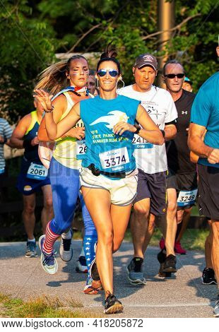 North Babylon, New York, Usa - 8 July 2019: A Femlae Runner Is Waving And Smiling For The Camera Whi