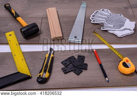 Equipment Or Tools To Install Laminate Floor. Hammer, Crowbar, Spacers, Cutter, Protective Gloves An