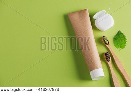 Wooden Toothbrushes, Organic Toothpaste, Dental Floss And A Leaf On Green