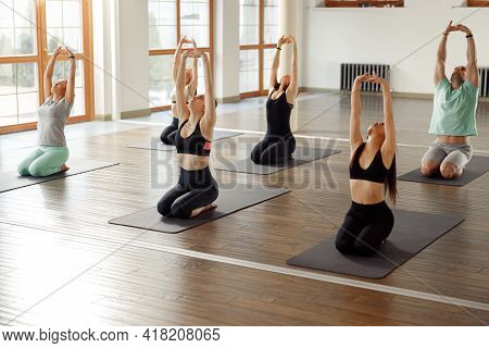 Young Sporty People In Yoga Class Making Meditation Exercises Together. Wellness Concept