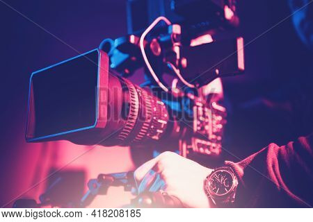 Modern Video Camera With Telephoto Lens And Camera Operator. Digital Motion Picture Equipment.