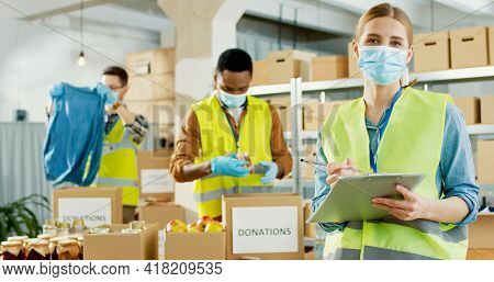 Portrait Of Young Caucasian Happy Female Volunteer In Medical Mask And Uniform Writing And Smiling T