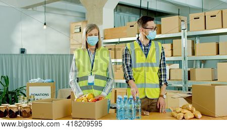 Caucasian Different Man And Woman Charity Workers Giving Food To Poor Multi-ethnic People At Social