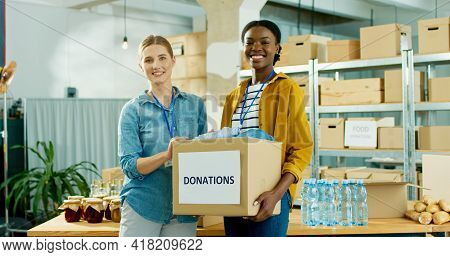 Young Mixed-race Happy Warehouse Workers Volunteers Working In Shipping Delivery Charitable Stock Or