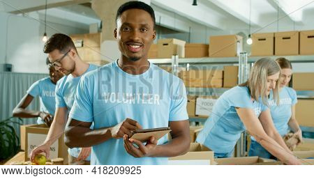 Close Up Portrait Of Cheerful Young African American Handsome Man In Good Mood Work In Charity Cente