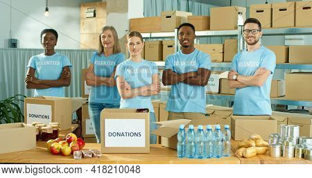 Multi-ethnic Cheerful Diverse Men And Women Social Workers Standing In Charity Organization Warehous