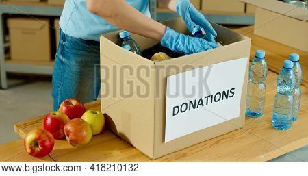 Close Up Of Caucasian Volunteer Hands In Gloves Packing Food Products In Donation Box For Poor Peopl