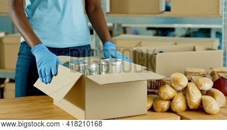 Close Up Of African American Social Worker Hands In Protective Gloves Packing Food Products In Donat