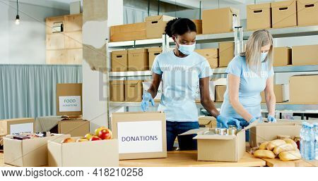 African American And Caucasian Female Volunteers Packing Donated Stuff And Food In Box Parcel With D